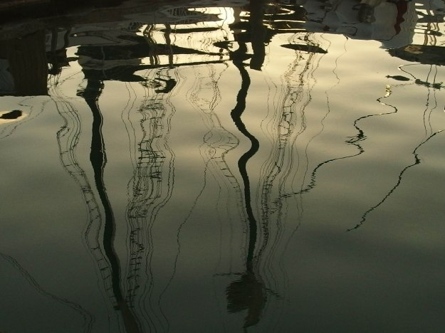 Image:  reflection of sailboat masts in the water.