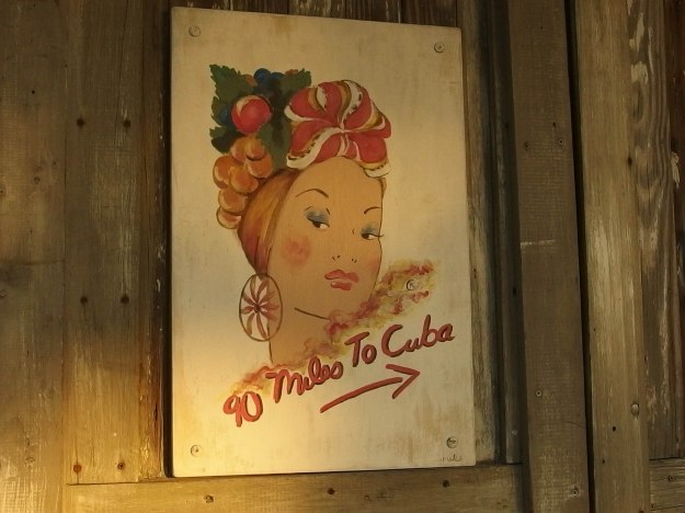 "Image: sign on a garage door with a drawing of a woman's head and face, wearing a hat made of fruit, with the legend ""90 miles to Cuba."""