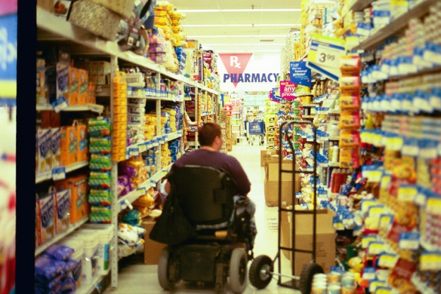 {Image:  A woman in a wheelchair wheeling away from the camera down a store aisle, the sides of which are clutered with boxes and a hand-truck.}
