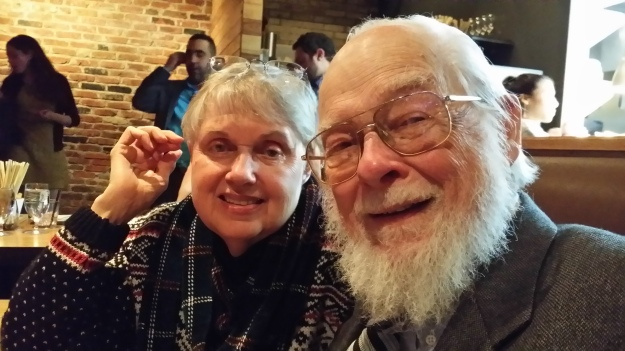 Image:  older white couple.  Woman on the left wearing a plaid scarf; man in the right with a full white beard and wire-framed glasses.