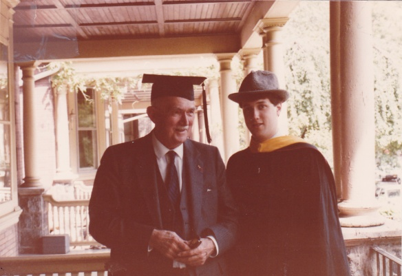 Image:  An older white man in a suit and tie who is wearing a graduation mortar board.  Standing next to him is a younger white man in a graduation cap and gown wearing the older man's fedora.