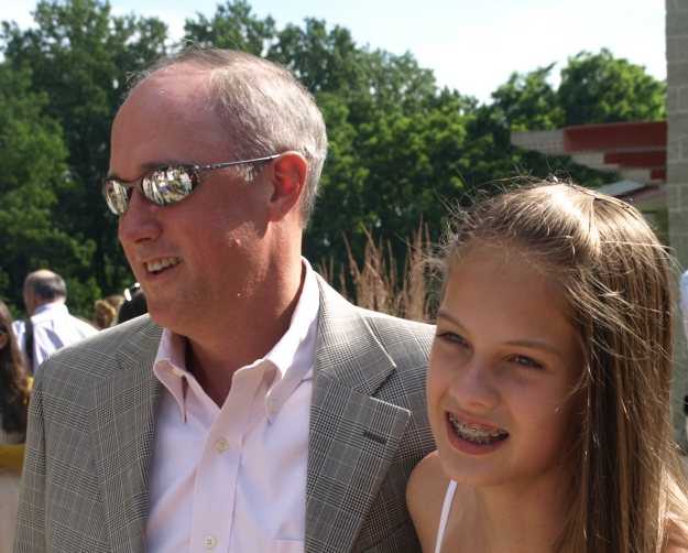 Image:  white man in his 40s wearing sunglasses, a sports coat and an open-collar shirt; next to him is a white girl with long light brown hair.