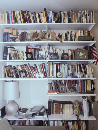 Image:  white bookshelves, filled with largely paperback books, in front of which are photos and mementos such as a pair of baseballs, a large piece of driftwood, an inlaid metal box, and an American flag.)
