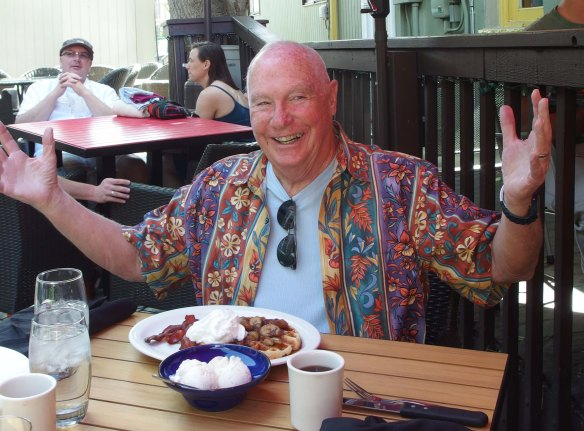 Image:  older white man in a flowered shirt sitting at an outdoor restaurant table, smiling with his arms outstretched.  On the table in front of him is a plate of waffles and bacon, with ice cream on top.