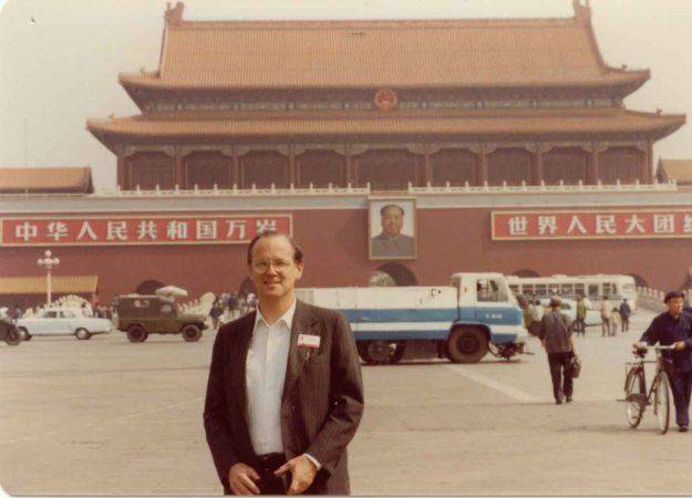 Image: Caucasian man standing in Tien An Men Square in Beijing in front of the iconic building from the Forbidden City with a giant portrait of Mao Tse Tung.