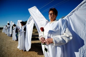 A woman dressed as an angel with large wings covered with white sheets standing next to others dressed similarly.