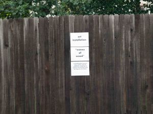 Image:  wooden fence with a sign consisting of three pieces of white paper stapled to it.