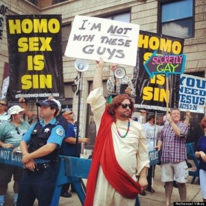 "Image:  Protesters holding signs reading ""Homo Sex is Sin.""  They are behind a police line. In the foreground, a white man dressed as Jesus Christ holds a sign saying ""I'm not with these guys.""  Another counterprotester holds a sign pointing to one of the protesters that says, ""Secretly Gay."""