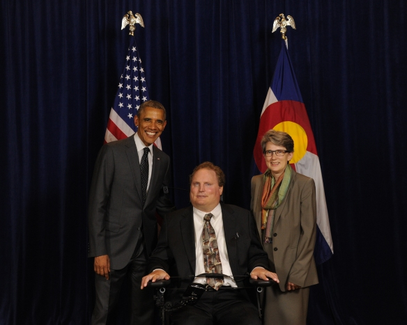 Image:  President Obama next to Tim Fox (white man in suit and tie sitting in wheelchair) and Amy Robertson (white woman in suit and scarf).