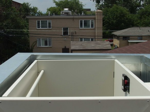 Image: View from top of open air wheelchair lift toward the houses beyond the roof deck.