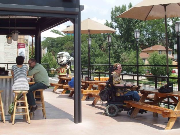 Image:  left side - a bar under an awning; right side - picnic tables with umbrellas.  A white man in a flowered shirt and using a wheelchair sits at one of the tables.