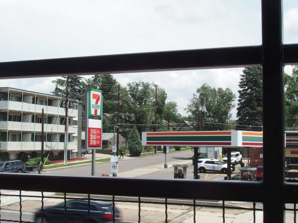Image: view over the railing of the roof deck to a 7-Eleven store.