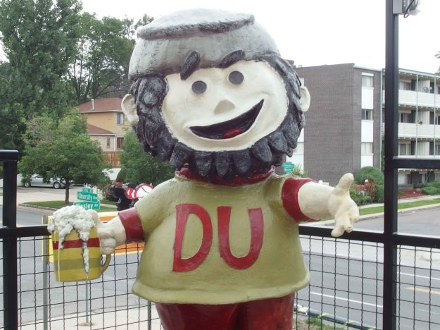 "Image: larger-than-life-sized figure of a ""pioneer"" a white guy with a beard and a DU sweatshirt, holding a stein of beer in one hand.  His arms are open to the roof deck and he is smiling."