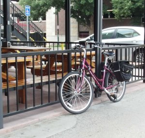 Image: photo of purple girl's bike locked to railing around patio in previous photo.