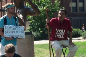 "Image:  An older white man wears a t-shirt that reads ""You Deserve Hell.""  Next to him, a younger white man holds a sign that reads, ""You can't choose to like dick but you can choose to be one.  For example"" and an arrow pointing to the guy in the You Deserve Hell t-shirt."