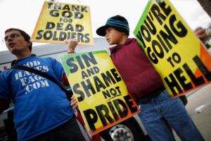 "Image:  Protesters (a white male adult and possibly light-skinned black child) holding signs that say ""Thank God for Dead Soldiers,"" ""Sin and Shame not Pride"" and ""You're Going to Hell."""
