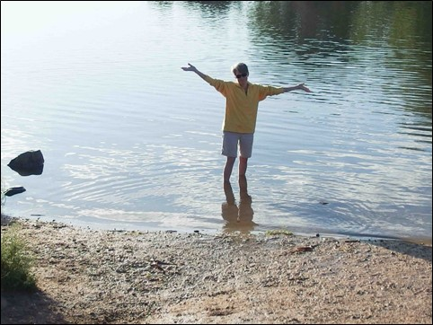 Image:  photo of woman in yellow fleece and khaki shorts standing in water with her arms outstretched.