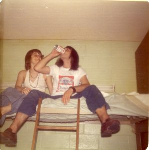 Image:  young white woman in a white halter top shirt is sitting on the top bunk of a bunk bed with a white man, 20-30 years old, wearing a Budweiser t-shirt and jeans, and drinking from a can of Budweiser beer.