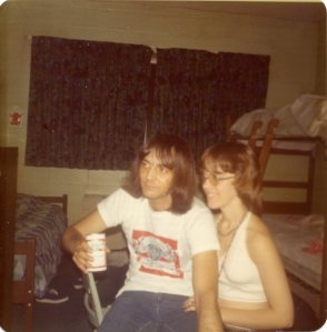 Image:  white man, 20-30 years old, wearing a Budweiser t-shirt and jeans, and holding a can of Budweiser beer shares a chair with a young white woman in a white halter top shirt.