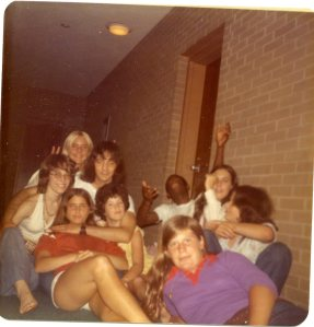 Image:  group photo in a dorm hallway, including 7 white girls ranging in age from 12 to 20, a 20-30 year old man (Dr. John), and a black teen-ager.