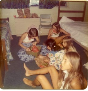 Image:  white woman in white halter top sitting on the floor of a dorm room eating watermelon and sharing it with four young white girls, apparently ranging in age from around 7 to perhaps 12.