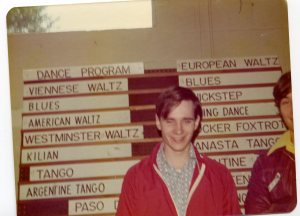 "Image:  Young white man in patterned shirt and red warm-up jacket poses in front of a sign-board listing dances by name (""waltz, tango, blues"")."