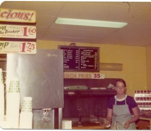 Image:  snack bar with white woman in apron behind the counter.  Sign reads French Fries 35 cents.