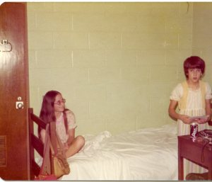 Image:  two approximtely 12-year-old white girls in pyjamas in a dorm room, one sitting on a bed, the other standing by a desk with a toothbrush.