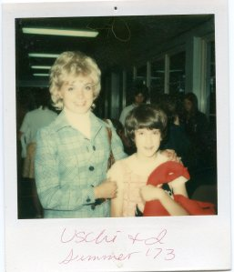 Image:  white woman with short, frosted white-blond hair, perhaps 30 years old, wearing a tourquoise polyester suit jacket with a young white girl with brown hair holding a stuffed lobster plush toy.