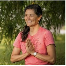 "Image: Asian woman wearing rose colored t-shirt smiling with hands together in front of her in ""namaste"" gesture."