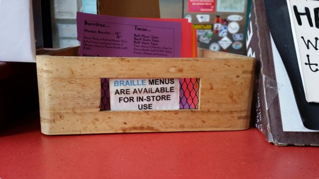 "Photo:  wooden box containing menus; a sign on the side reads ""Braille menus are available for in-store use."""