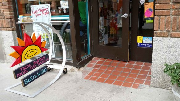 "Photo:  Sidewalk sign showing a big, wooden sun with attached smaller signs reading ""Tacos Burritos Nachos Fish Tacos and more"" and another reading ""Beer and Wine.""  Next to the sign, a door into a restaurant with a sloped tile ramp leading in."