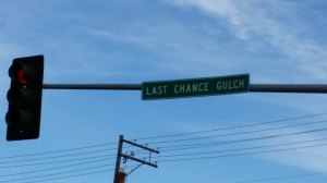 "Photo:  traffic light and street sign reading ""Last Chance Gulch."""