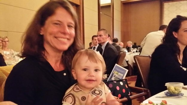 Image: white woman sitting at a dinner table holding a white toddler, both smiling for the camera.