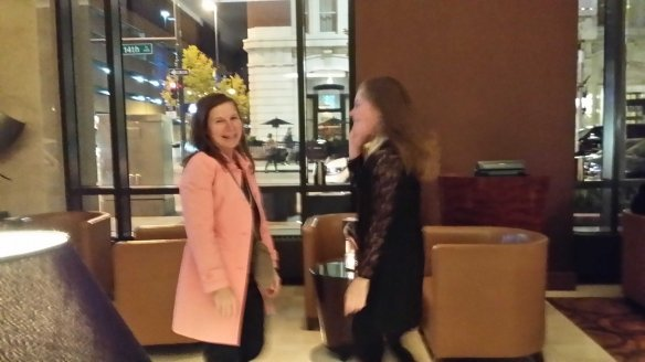 Image: slightly blurry photo of white woman in pink coat dancing with blond girl (from photo 2 above) in a black dress.