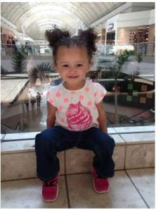 Image:  mixed race toddler girl in pick polka-dot t-shirt and jeans sitting in what appears to be a shopping mall.