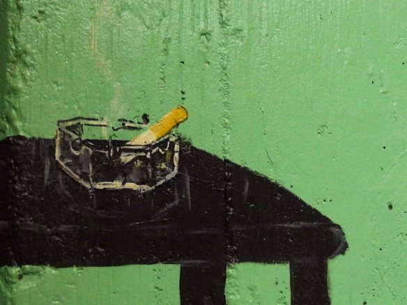 Photo of detail from a painted outdoor wall showing an ashtry with a half-smoked cigarette.