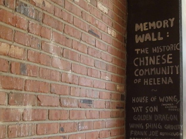 "Photo of a brick wall and text painted on the adjacent wall reading, ""Memory Wall:  The Historic Chinese Community of Helena."""