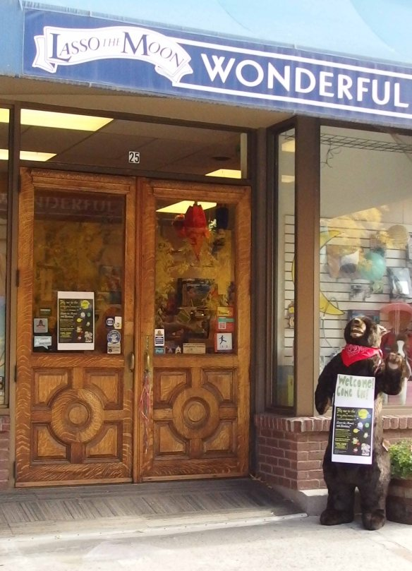 Photo:  front of a toy store with a large stuffed bear, accessible with a sloped entryway.