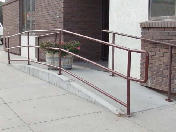 Photo of two-way ramp in front of the door to an office building with a giant flower pot at the top of the ramp.