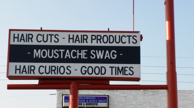 "Image: large commercial sign reading ""hair cuts.  hair products.  moustache swag. hair curios. good times."""
