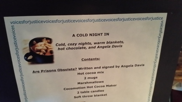 "Image:  photo of a sign reading, ""A cold night in:  Cold, cozy nights, warm blankets, hot chocolate, and Angela Davis.  Contents:  ""Are Prisons Obsolete?"" written and signed by Angela Davis; hot cocoa mix; 2 mugs; marshmallows; cocomotion hot cocoa maker; 2 table candles; soft throw blanket."