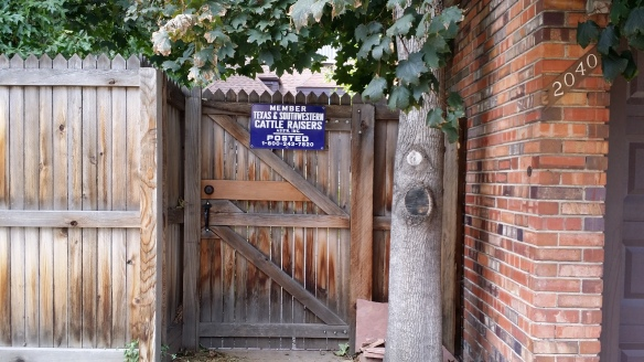 """Image:  Wooden fence with a sign reading """"Member Texas & Southwestern Cattle Raisers Ass'n Inc.  POSTED."""