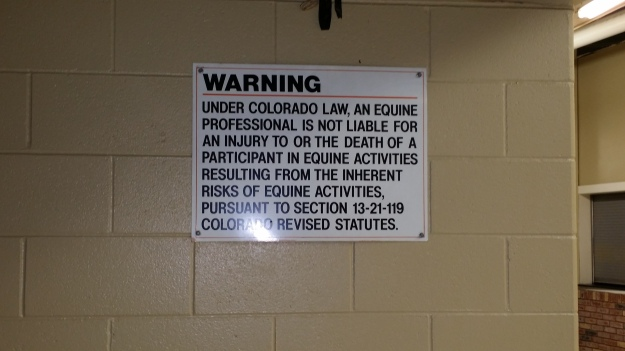 "Image:  Sign affixed to a cinderblock wall that reads, ""WARNING  Under Colorado law, an equine professional is not liable for an injury to or the death of a participant in equine activities resulting from the inherent risks of equine activities pursuant to Section 13-21-119 Colorado Revised Statutes. """