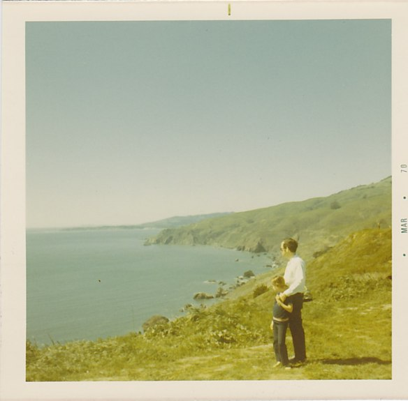 Photo:  A man and a girl (about 10) stand on the shore facing the water.  The man is in a white shirt and dark pants; the girl is in a blue shirt and pants.  The man has his hand on the girl's shoulder.