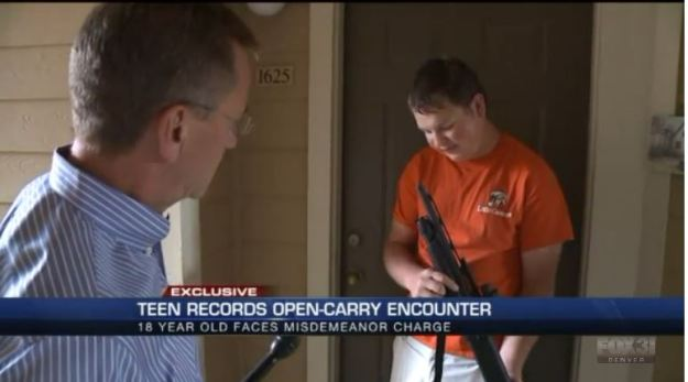 "Image: snip from local news showing reporter on the left (white; male; salt & pepper hair) talking to white teenager with shot gun.  Caption reads ""Teen Records Open-Carry Encounter.  18 year old faces misdemeanor charge."""