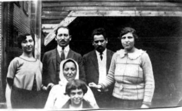Image:  slighly blurry black & white photo of a group of 6 people.  In back, a young woman, two middle aged men and a middle aged woman; in front of them, an older woman, and in front of her, a child of about 10.