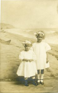 Image:  sepia photo of two young blond girls in white dresses with white ribbons in their hair, standing in front of a painting or backdrop of a beach with a rowboat.