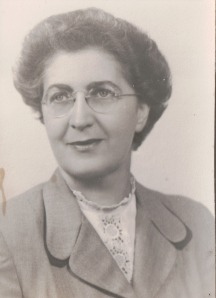 Image:  black & white photo of a middle-aged woman with short salt & pepper hair and wire-rimmed glasses, wearing a suit jacket and a lace blouse underneath