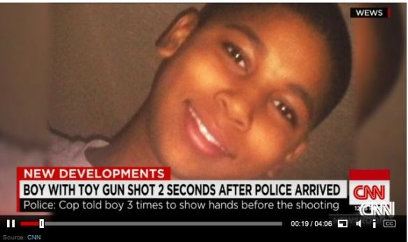 "Image:  clip from newscast with photo of black boy with caption ""Boy with toy gun shot 2 seconds after police arrived.  Police:  cop told boy 3 times to show hands before the shooting."""